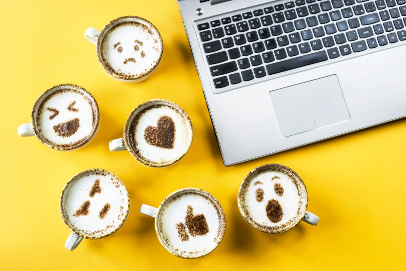 emoji on cups next to the laptop